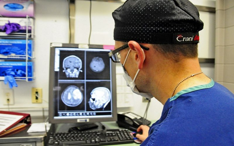 U.S. Air Force Maj Jonathan Forbes, 455 Expeditionary Medical Operations Squadron neurosurgeon reviews magnetic resonance imaging of a patient prior to performing brain surgery at the Craig Joint Theater Hospital, Bagram Air Field, Afghanistan, Oct. 10, 2014.  Forbes removed an 8 centimeter tumor in surgery that lasted 5 hours. Forbes is from Travis Air Force Base, Calif. (U.S. Air Force photo by Staff Sgt. Miguel Lara III/Released)